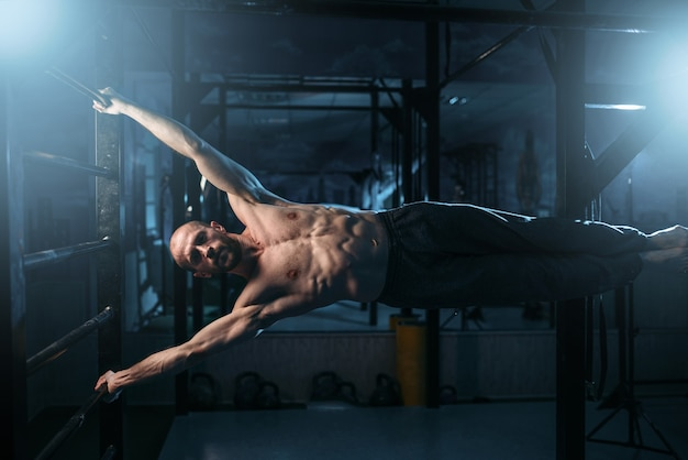 Спортсмен с мускулистой фигурой прилагает усилия для сохранения горизонтального баланса на перекладине.