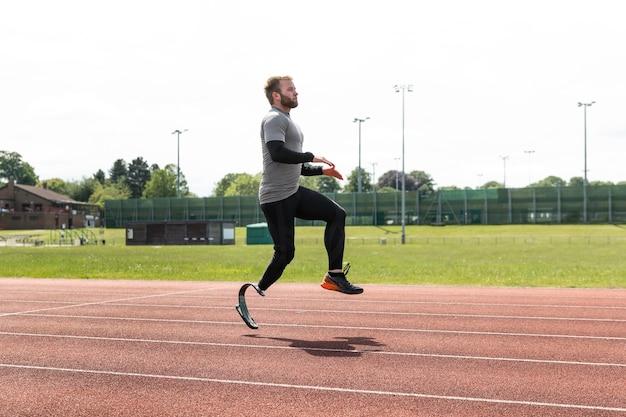 Atleta con protesi che salta a tutto campo