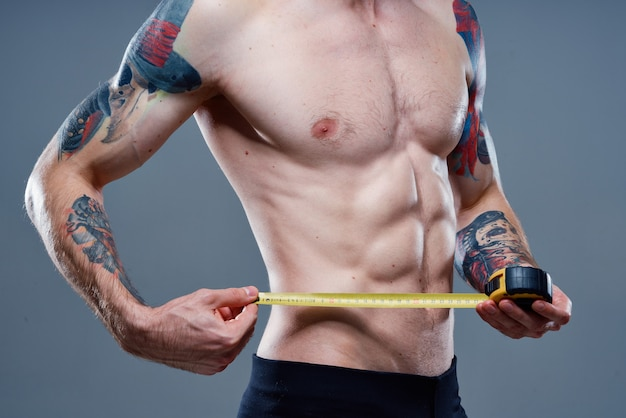 Athlete with pumped up arm muscles and tattoos bodybuilder fitness centimeter tape