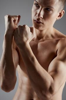 筋肉モデルの灰色の背景のトリミングされたビューにポンプアップされた胴体ボクシングを持つアスリート