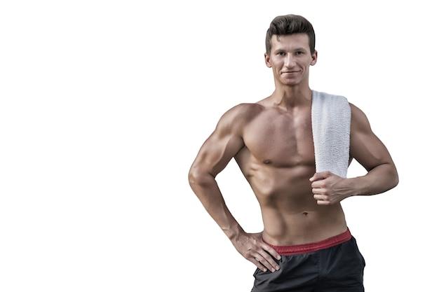 Спортсмен с сильными руками, бицепсами и трицепсами. спортсмен улыбается с полотенцем на белом фоне. фитнес и спорт. человек с голым торсом с шестью пакетами и ab. концепция гигиены и здоровья, копия пространства
