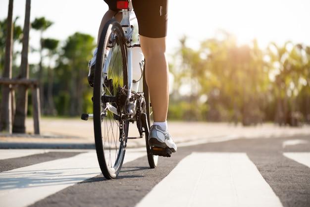 Ноги велосипедиста женщины спортсмена ехать горный велосипед на дороге в утре.