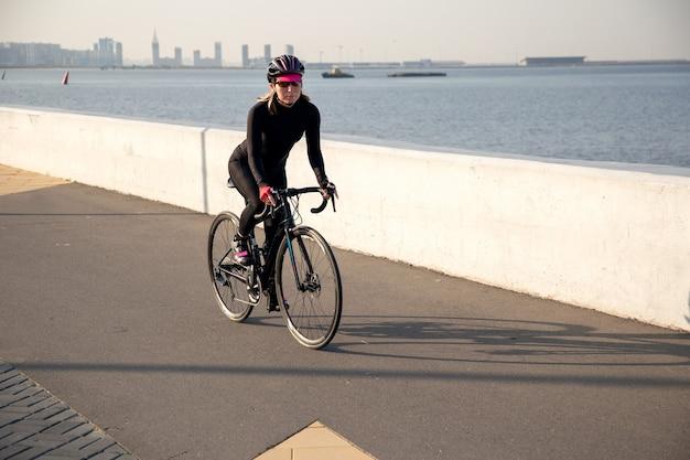 Спортсменка женщина-велосипедист тренируется вдоль набережной на рассвете