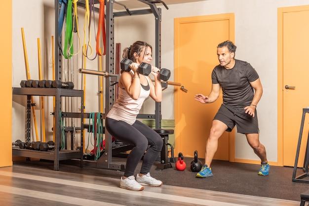 트레이너의 도움으로 체육관에서 아령으로 쪼그리고 앉는 운동 선수. 체육관에서 장비와 운동의 개념입니다.