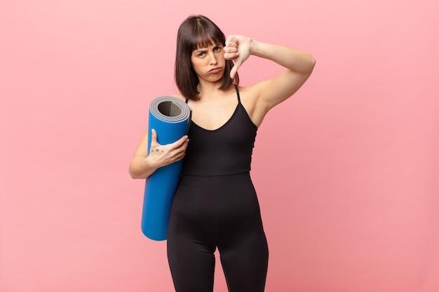 Женщина-спортсменка чувствует раздражение, злость, раздражение, разочарование или недовольство, показывая большие пальцы вниз с серьезным взглядом