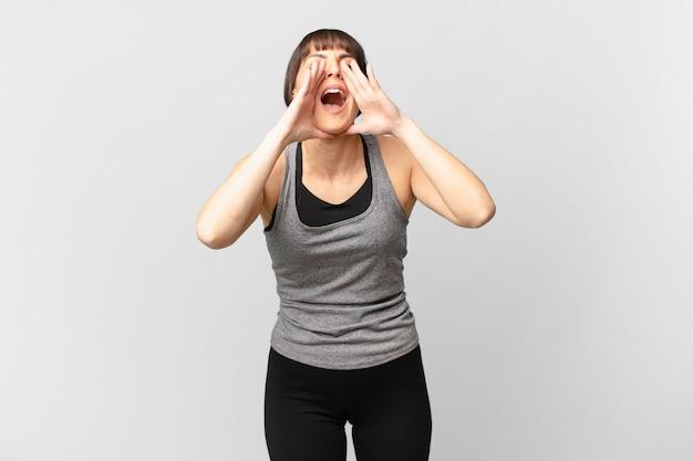 Женщина-спортсменка чувствует себя счастливой, взволнованной и позитивной, громко кричит, держа руки рядом со ртом, выкрикивая