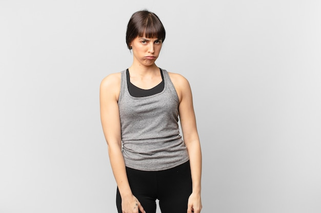Женщина-спортсменка грустит, расстроена или злится и смотрит в сторону с отрицательным отношением, хмурясь в знак несогласия