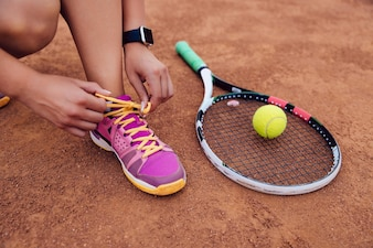 Athlete woman getting ready for playing a game of tennis, tying shoelaces.