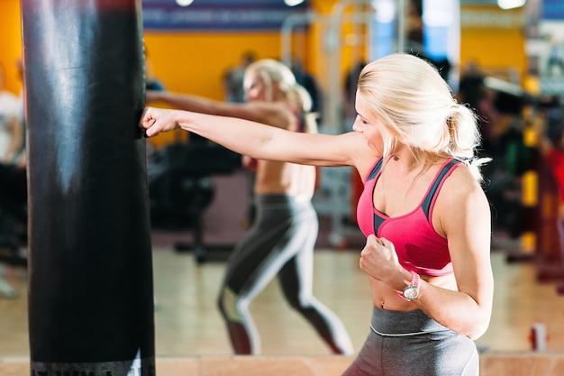 Спортсмен женщина, ударяющая боксерскую грушу в тренажерном зале