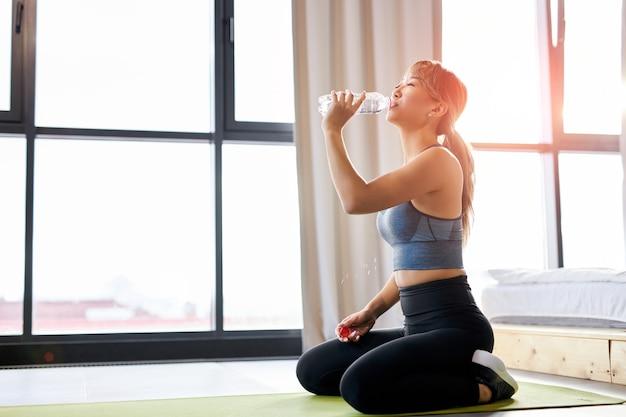 明るい部屋で、スポーツ運動後の水を飲むスポーツウェアの運動選手の女性。モチベーション、スポーツコンセプト