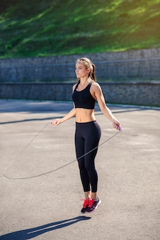 Athlete woman jumping with skipping rope at stadium