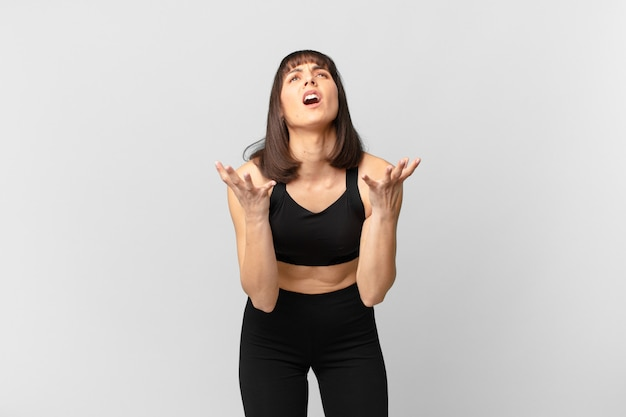 Athlete woman looking desperate and frustrated, stressed, unhappy and annoyed, shouting and screaming