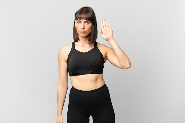 Athlete woman looking serious, stern, displeased and angry showing open palm making stop gesture