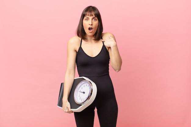 Athlete woman looking shocked and surprised with mouth wide open, pointing to self