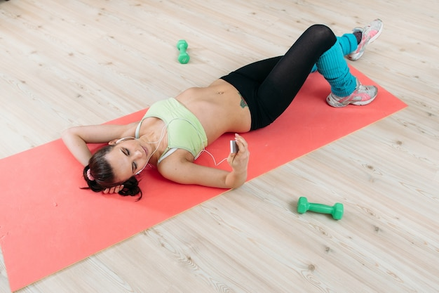Athlete woman resting on mat listening music in gym