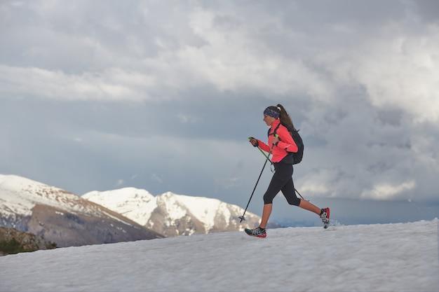 アスリートの女性が雪の上を走る