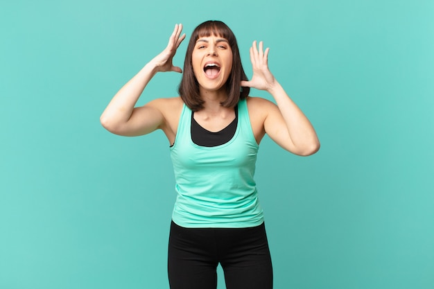 Athlete woman screaming with hands up in the air, feeling furious, frustrated, stressed and upset