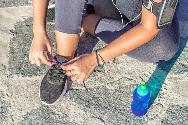 彼女の靴ひもを結ぶ床に座っている運動選手の女性