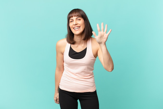Athlete woman smiling and looking friendly, showing number five or fifth with hand forward, counting down