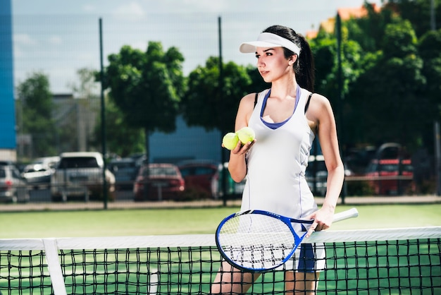 Athlete woman in sportswear holding racket and balls