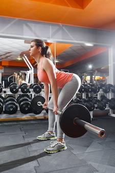 Тренировка женщины спортсмена с металлической штангой в тренажерном зале