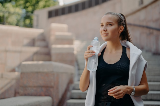 Athlete woman with pony tail feels thirsty after cardio training drinks water from bottle holds refreshig drink stays hydrated poses outdoors dressed in active wear concentrated into distance