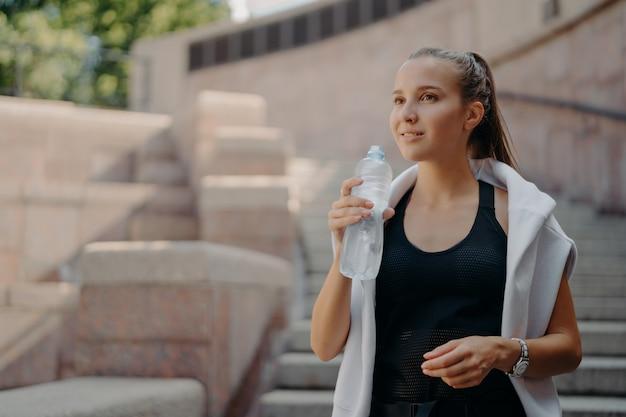조랑말 꼬리를 가진 운동 선수 여자는 심장 훈련이 병에서 물을 마신 후 목이 마른 느낌이 든다.