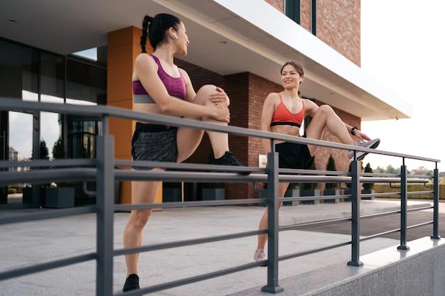 Спортсменки готовятся к бегу по улице города. согревание и растяжка ног. спортивная обтягивающая одежда. по горизонтали. 30-е годы
