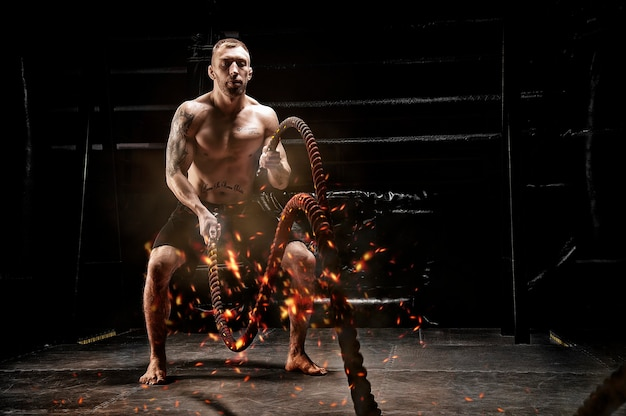 The athlete works with crossfit ropes in the gym. flames, sparks and smoke. the concept of sports, bodybuilding, fitness. mixed media