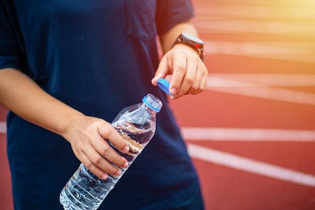 Спортсмены находятся на беговой дорожке и открывают бутылку с водой рукой