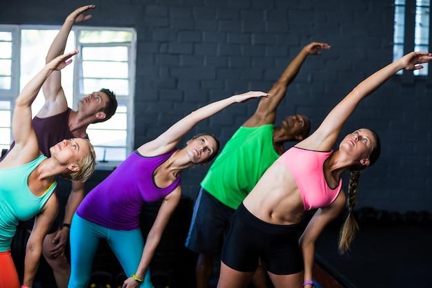 Athletes bending while exercising in gym