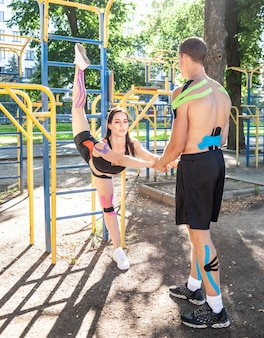 Athletes couple with colorful kinesiology elastic taping on bodies