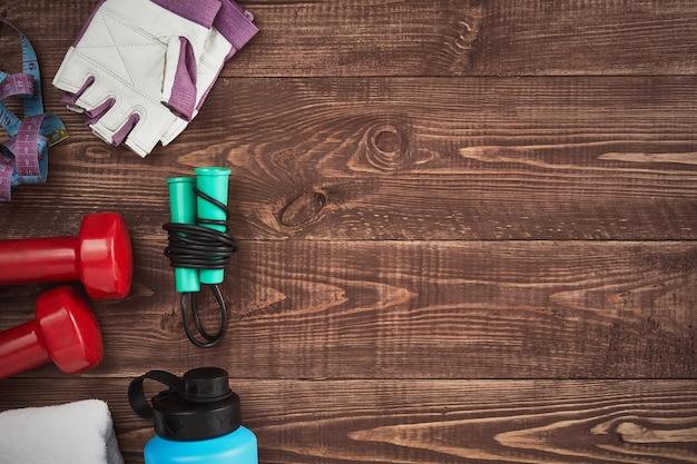 アスリート機器ダンベルスポーツウォーターボトルは、木製の背景に縄跳びスニーカー