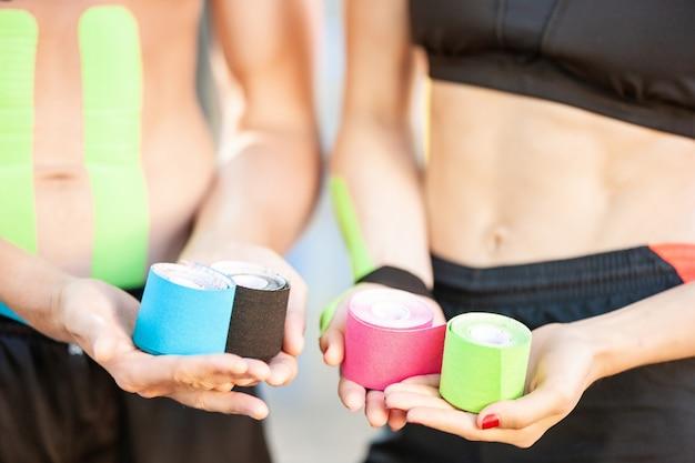 운동 선수들은 탄성 운동 요법 테이프의 다채로운 롤을 들고