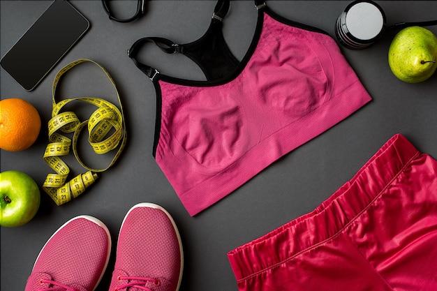 회색 배경에 여성용 운동화와 물 한 병을 넣은 운동선수