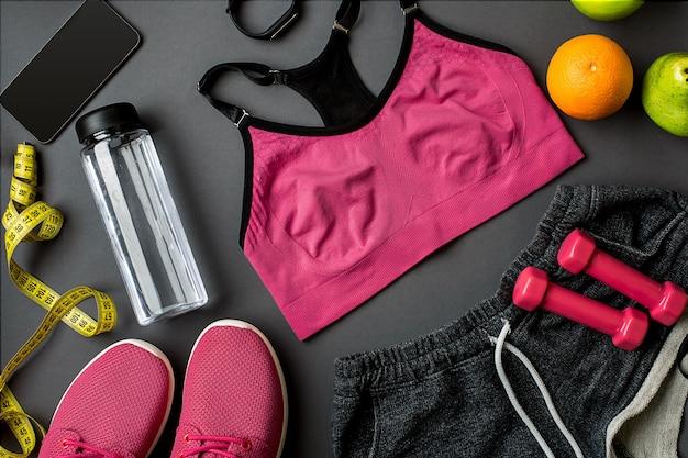 회색 배경에 여성용 운동화와 물 한 병을 넣은 운동선수 프리미엄 사진