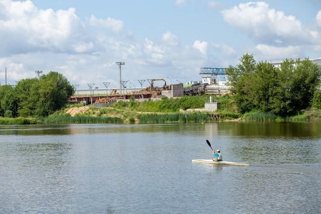 Спортсмены тренируются в байдарках по реке на фоне промышленного предприятия
