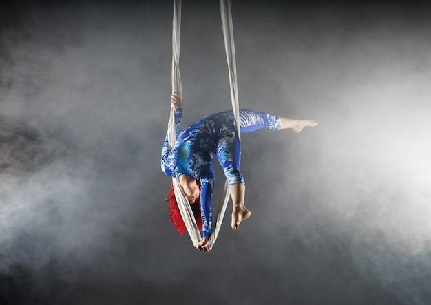 공중 실크에 한 손으로 서있는 파란색 의상에 빨간 머리가있는 운동 공중 서커스 아티스트