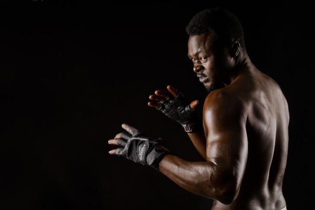 Спортивный (ый) африканский боец на черной поверхности