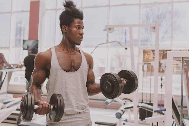 Athletic african man working out with dumbbells at the gym
