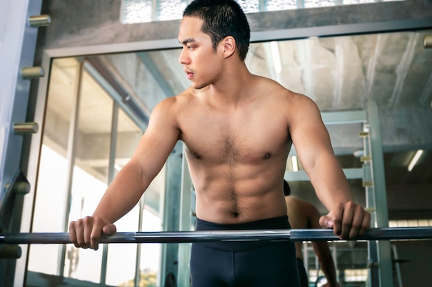 Athletic asian man fit and healthy smiling in gym after workout.