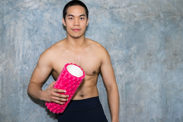 Athletic asian man using a foam roller after a workout.