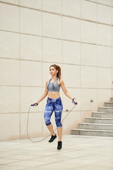 Athletic asian woman jumping with skipping rope outdoors