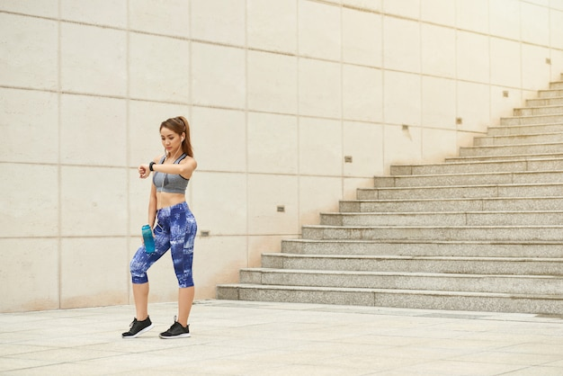 Athletic asian woman standing outdoors with water bottle and looking at wristwatch