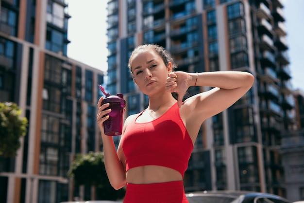 スポーツボトルを保持し、親指を下に赤いスポーツウェアを身に着けている茶色のポニーテールを持つ運動の魅力的な不満の若い女性