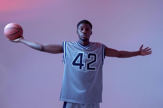 アスレチックバスケットボール選手は、スタジオ、ネオンの背景にボールを持ってポーズします。スポーツゲームをするスポーツウェアのプロの男性バラー、背の高いスポーツマン