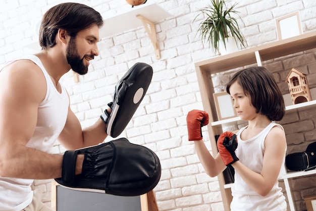 Athletic bearded father teaches son to box.