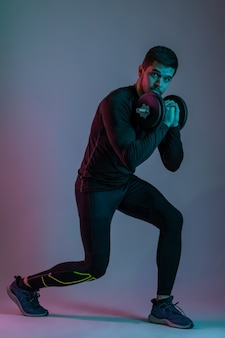 Athletic bearded guy doing split squats with dumbbell