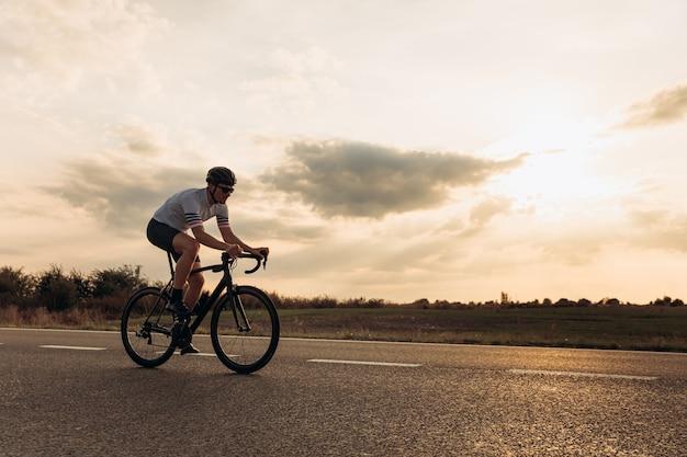 스포츠 의류 및 아스팔트 도로에 자전거를 타고 보호 헬멧에 운동 수염 남자