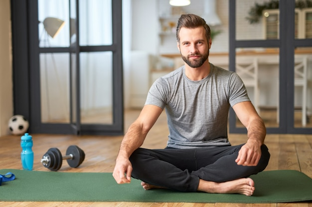 カメラを見て、床に蓮華座に座って笑っている運動ひげを生やした男